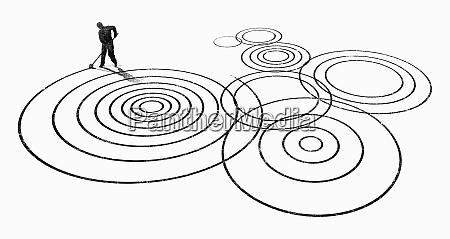 man making zen garden circles