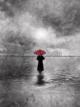 stimmungsvolle einzelfrau mit rotem regenschirm waten