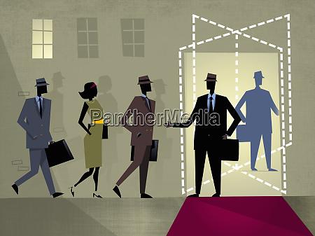 businessman welcoming businesspeople at revolving door