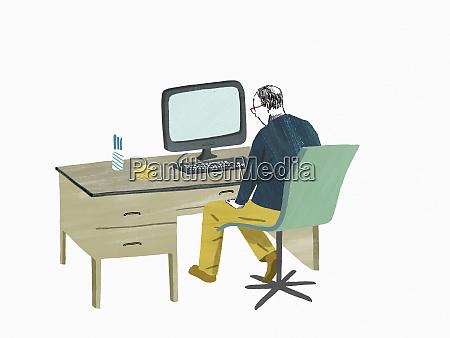 elderly man sitting at desk using