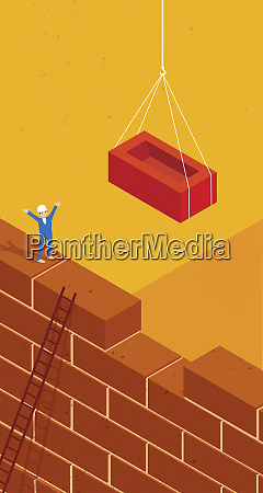 construction worker guiding large brick into