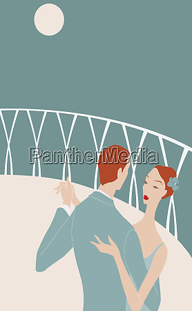 romantic couple dancing on balcony at