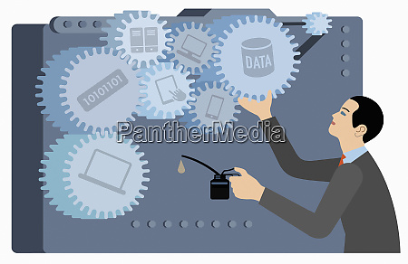 businessman oiling the cogs of computer