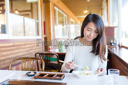 woman enjoy japanese barbecue in restaurant