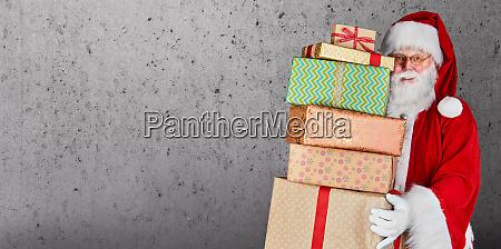 weihnachtsmann haelt geschenke mit kopierplatz