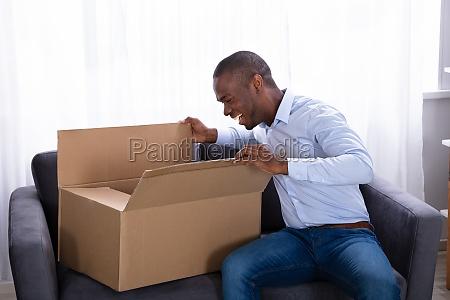 happy man looking inside package