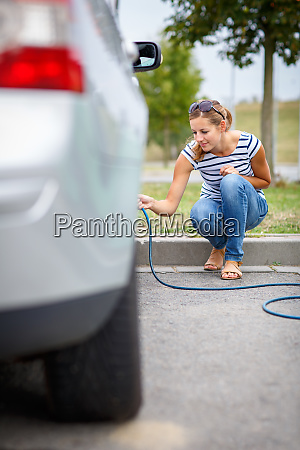young woman checking the car tyre