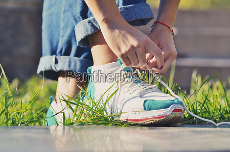 young girl wearing jeans tying shoelaces
