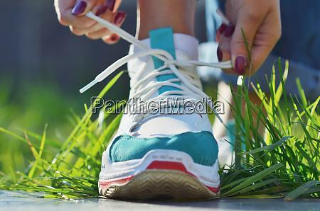 young girl tying shoelaces on sneaker