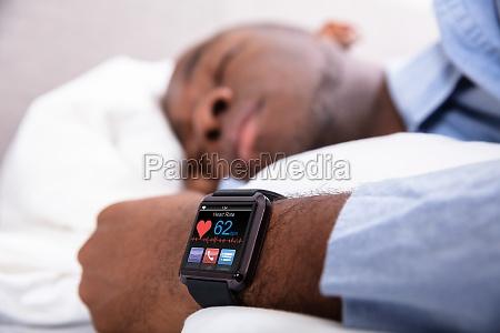mann schlaeft mit smart watch in
