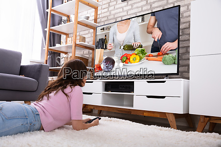young woman watching television at home