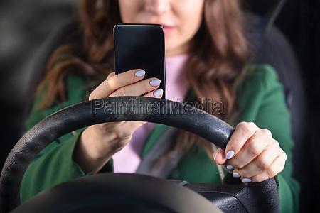 frau faehrt mit smartphone mit auto