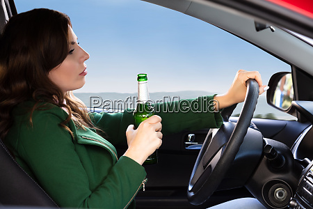 woman holding beer bottle while driving