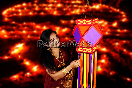 indian woman admiring her diwali lantern