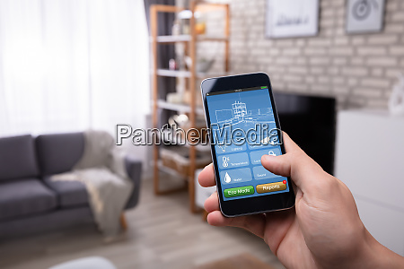 man using smart home application on