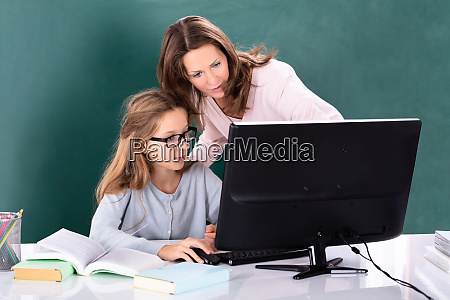 teacher teaching her student on computer