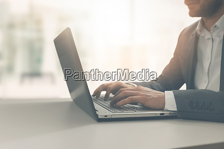 young man typing on laptop in
