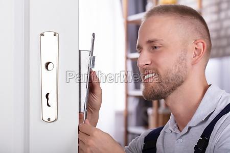 nahaufnahme eines mannes fixing door lock