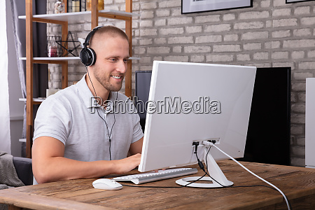 man using headphone while working on