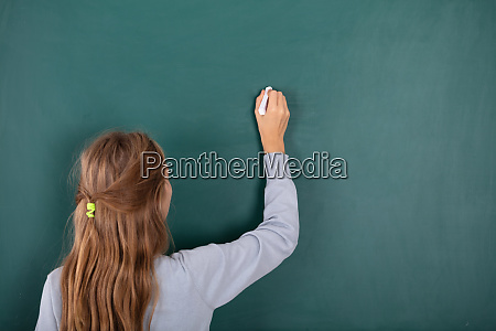 female student writing with chalk on