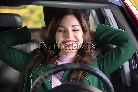 woman stretching her arms in car