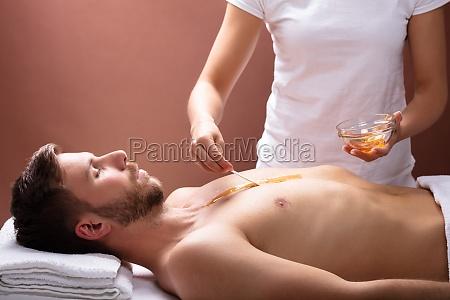 therapist applying wax on mans chest