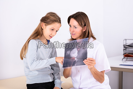 girl looking at doctor holding bone