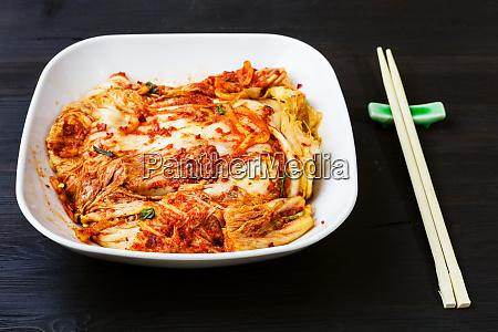 kimchi in weisser schuessel und essstaebchen