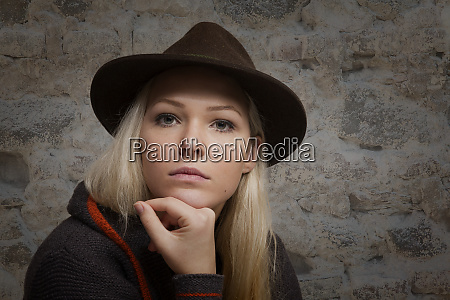 pensive young woman with brown hat