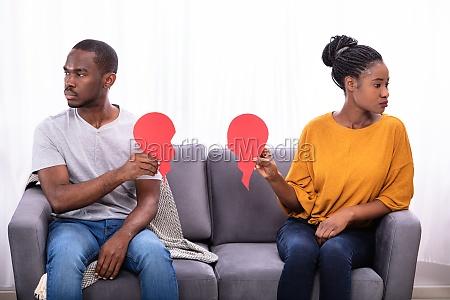 couple sitting on sofa holding broken