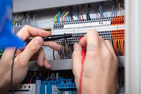 maennlicher elektro pruefkasten mit multimeter