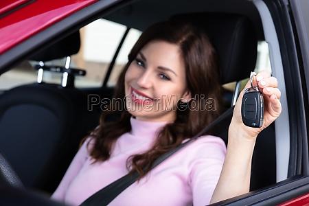 frau sitzt im auto zeigt schluessel