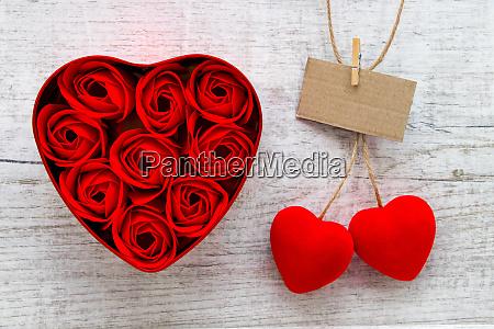 rote rosen in einer herzfoermigen kiste