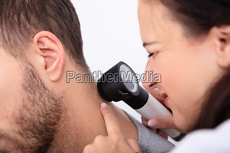 doktor prueft skin am menschenkneck