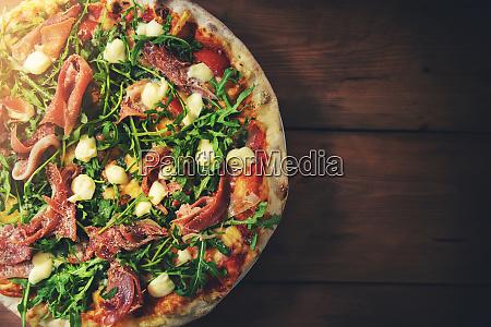 prosciutto arugula pizza on brown wooden