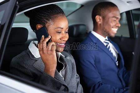 glueckliche geschaeftsfrau sitzt im auto auf