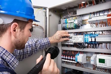 elektriker untersucht eine sicherungsbox