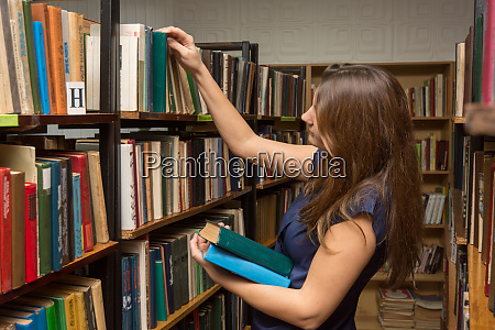 young girl chooses books in the
