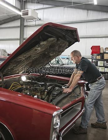 a senior car mechanic working on