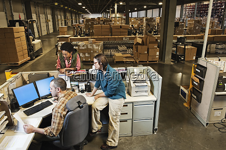 three mixed race warehouse workers studying