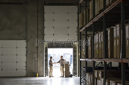 two warehouse workers shaking hands while
