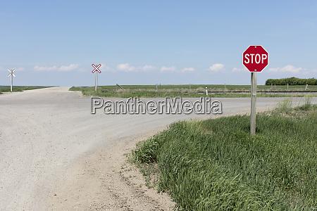 stoppschild und bahnuebergang entlang der landstrasse