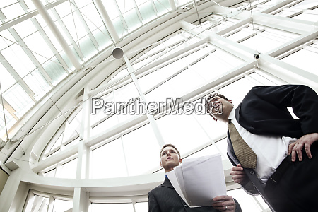 two businessmen going over paperwork in