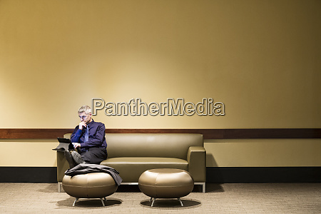 caucasian businessman sitting at a couch