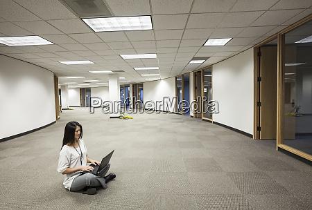 an asian businesswoman sitting cross legged