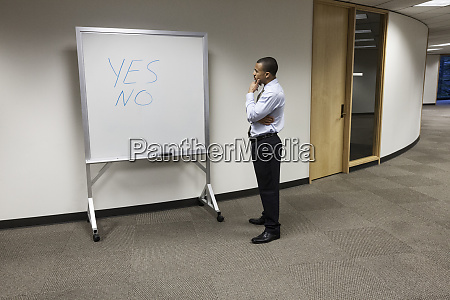 a black businessman thinking and standing