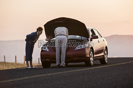 senior couple with car engine problems