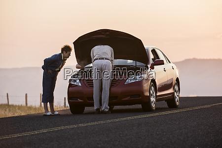 senior couple with car engine problems