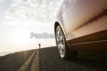 an automobile approaching a person standing