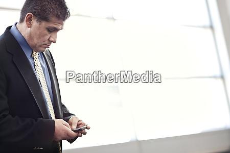 hispanic businessman checking his cell phone